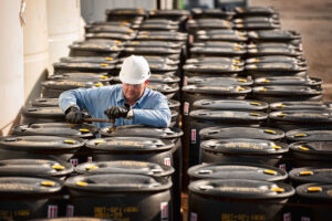 Supervisor checking barrels of chemicals