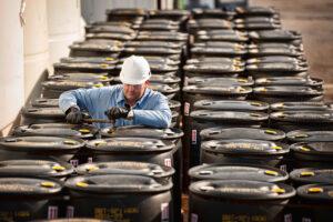 Supervisor checking barrels of chemicals
