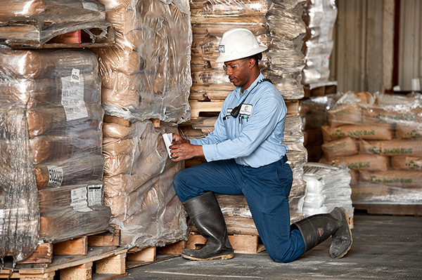 man in warehouse inspecting oilfield chemicals in palettes